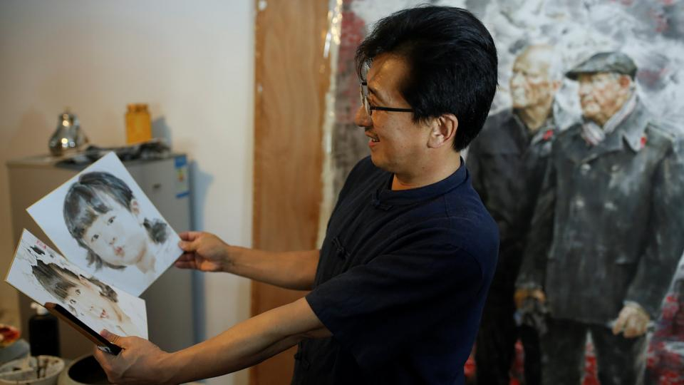 The head of the Mansudae Art Museum Ji Zhengtai talks about paintings by a North Korean artist in the studio of the gallery in Beijing. September 20, 2017.