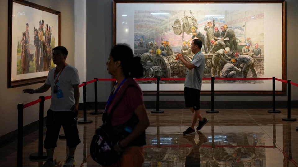 People looking at paintings created by North Korean artists in China-North Korea Cultural Centre in Dandong, China. September 9, 2017.