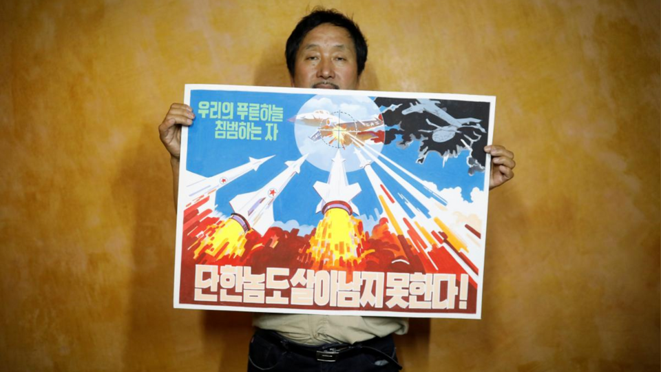 Head of Gallery Pyongyang showcases an example of North Korean propaganda art reading