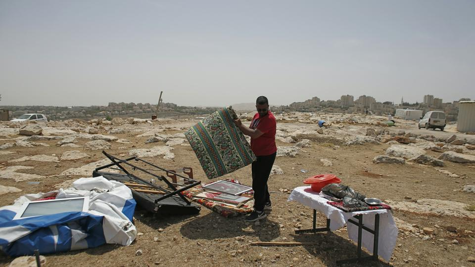 A Palestinian Bedouin man collects his belongings after Israeli Army forces dismantled a number of prefab houses, built with a donation from the European Union, in the West Bank Area B town of Al Azariya, east of Jerusalem, on May 16, 2016. (AFP)