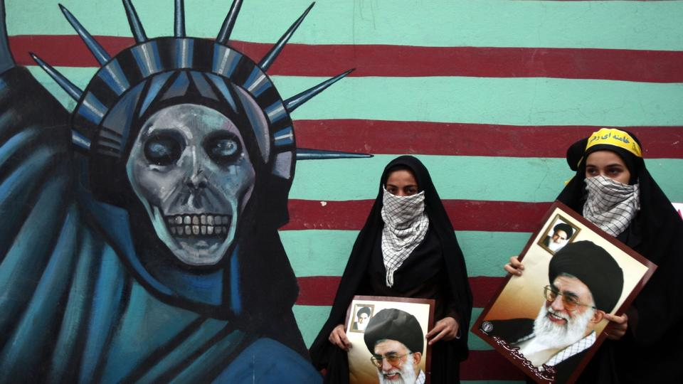 Iranian women hold pictures of Supreme Leader Ayatollah Khamenei outside the former US embassy in Tehran, Nov. 4, 2011, during a rally to mark the storming of the American embassy by Iranian students in 1979 .