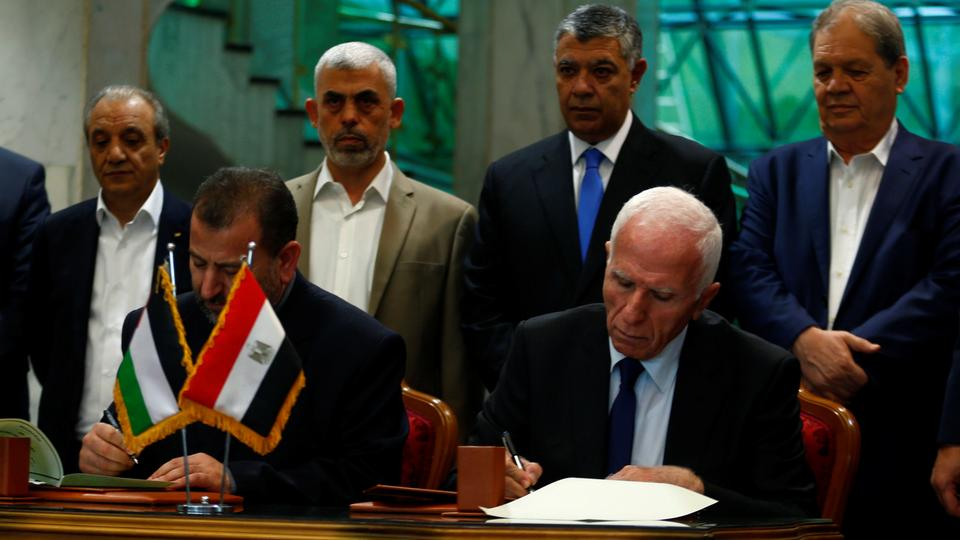 Head of Hamas delegation Saleh Arouri and Fatah leader Azzam Ahmad sign a reconciliation deal in Cairo, Egypt, October 12, 2017.