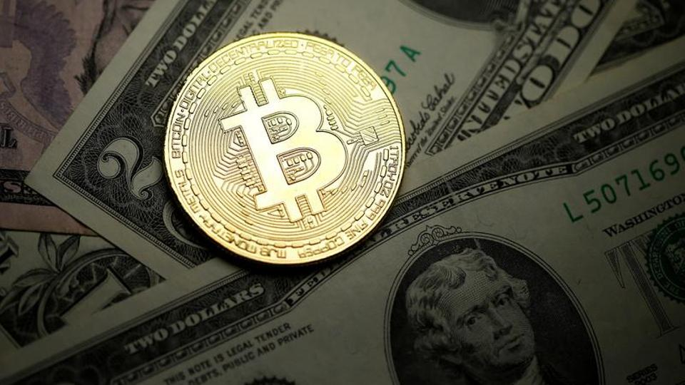 A Bitcoin and dollar notes are seen in this illustration picture taken on September 27, 2017. (Reuters)