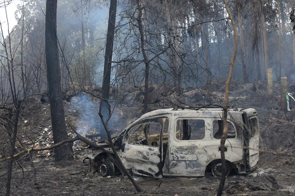 The wreckage of a burned van where two people died trapped by flames is pictured in Chandebrito, near the town of Nigran, northwestern Spain, on October 16, 2017.