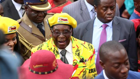 Sacked Zimbabwe vice president goes into exile, vows to defy Mugabe