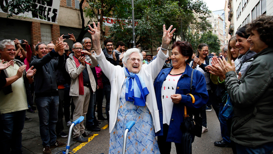 In this Sunday, Oct. 1, 2017 photo, an elderly lady is applauded as she celebrates after voting at a school assigned to be a polling station by the Catalan government at the Gracia neighborhood in Barcelona, Spain.