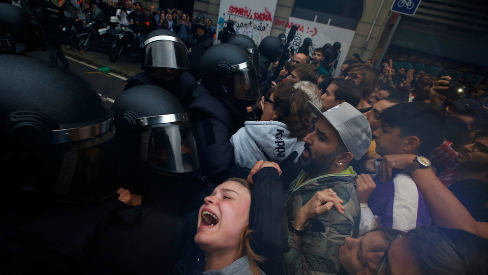 In this Sunday, October 1, 2017 photo a girl grimaces as Spanish National Police pushes away pro-referendum supporters outside the Ramon Llull school assigned to be a polling station by the Catalan government in Barcelona, Spain.