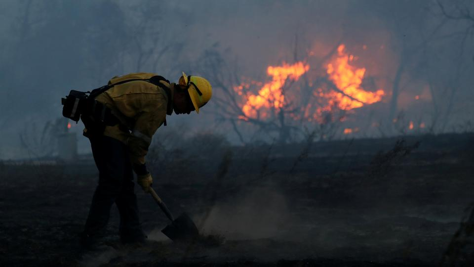 A firefighter works to put out hot spots on a fast moving wind driven wildfire in Orange, California. (Reuters)