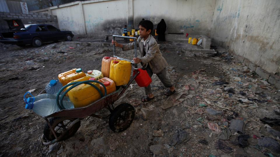 A boy pushes a wheelbarrow filled with water containers after collecting drinking water from a charity tap amid a cholera outbreak in Sanaa