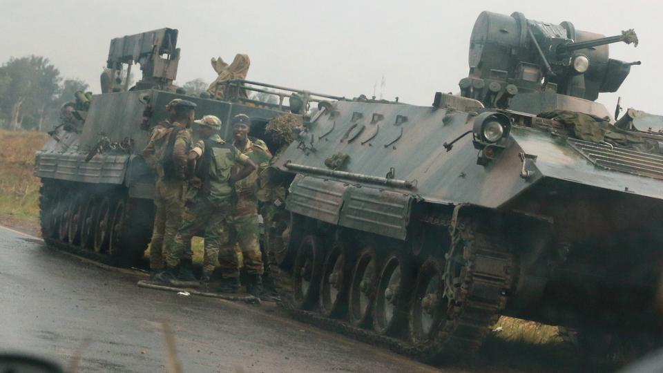 Soldiers stand beside military vehicles just outside Harare on Tuesday.