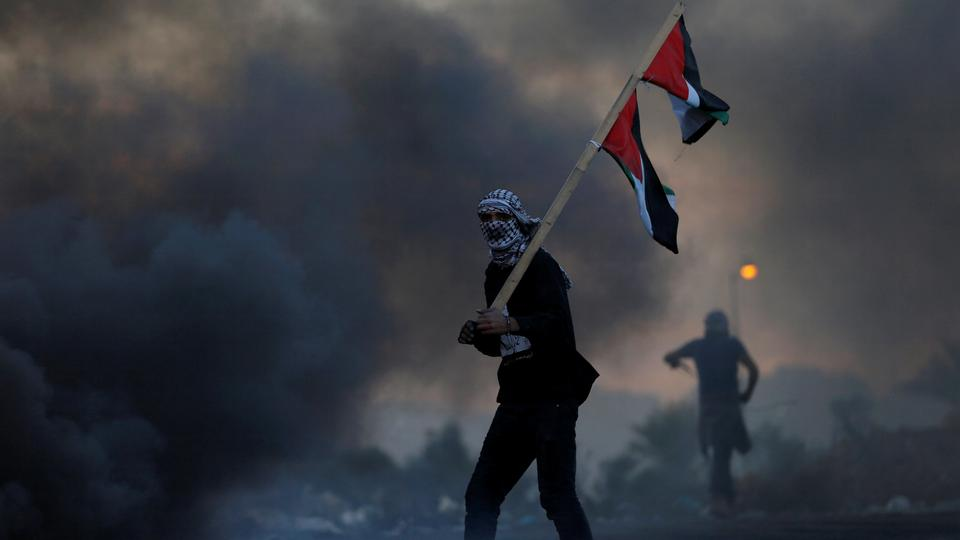 A demonstrator holds a Palestinian flag during clashes with Israeli troops at a protest against U.S. President Donald Trump's decision to recognize Jerusalem as Israel's capital near the Jewish settlement of Beit El near the West Bank city of Ramallah D