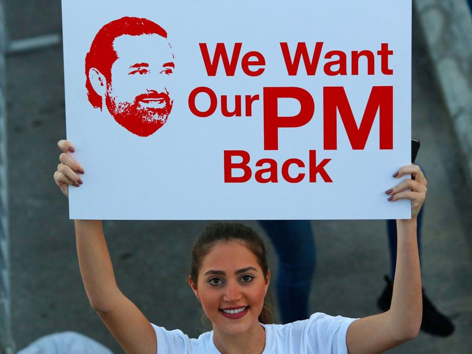 A woman holds a placard supporting the return of Lebanese prime minister from Saudi Arabia, during a marathon in capital Beirut on November 12, 2017.