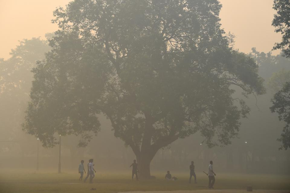 This file photo taken on October 20, 2017 shows Indian men playing cricket amid heavy smog in New Delhi on the day after the Diwali Festival. Unprecedented scenes of Sri Lankan cricketers wearing face masks has reignited debate about hosting major sports in heavily polluted New Delhi, where doctors are increasingly vocal about the health risks posed by smog.