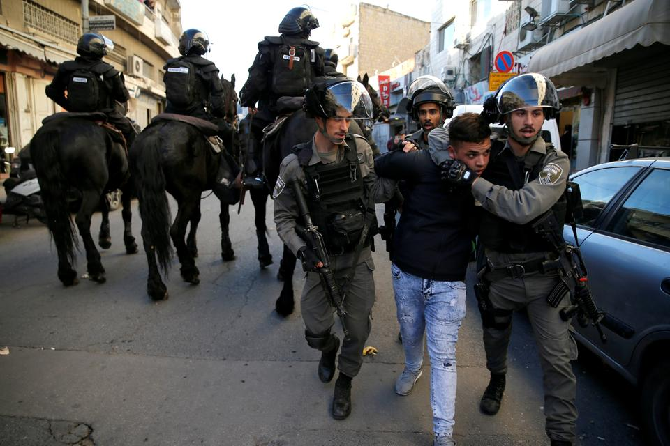 Israeli border police officers detain a protestor during a demonstration in a street in east Jerusalem